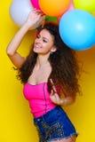 Jong en mooi krullend meisje in een roze overhemd en blauwe borrels o Stock Foto's