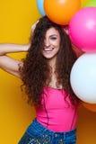 Jong en mooi krullend meisje in een roze overhemd en blauwe borrels op een gele achtergrond die kleurrijke ballons en het lachen  Royalty-vrije Stock Afbeelding