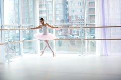 Jong en ongelooflijk stelt de mooie ballerina en danst in een wit studiohoogtepunt van licht Royalty-vrije Stock Foto's