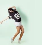 Jong energiek sporten actief meisje die in de Studio op een lichte achtergrond in t-shirt en borrels dansen stock fotografie