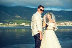 Jong enkel echtpaar in huwelijkskleding en kostuum bij de kust met bergen op achtergrond Stock Fotografie