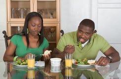 Jong etnisch paar dat door lijst ontbijt eet Royalty-vrije Stock Foto