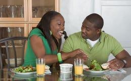 Jong etnisch paar dat door lijst ontbijt eet Stock Foto's