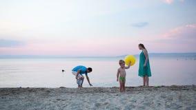 Jong familie speeltennis bij de kust stock video