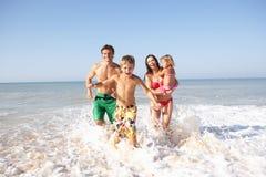 Jong familiespel op strand Stock Foto's