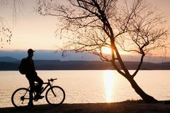 Jong fietsersilhouet op blauwe hemel en zonsondergangachtergrond op strand Eind van seizoen bij meer stock afbeelding