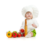 Jong geitje in chef-kokhoed met gezonde voedselgroenten stock afbeeldingen