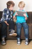 Jong geitje dat aan een tabletcomputer werkt Stock Foto's