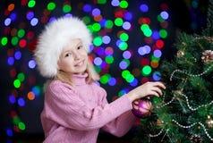 Jong geitje dat Kerstboom op heldere achtergrond verfraait Royalty-vrije Stock Foto's
