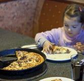 Jong geitje dat pizza op restaurantachtergrond eet Royalty-vrije Stock Foto