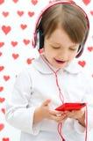Jong geitje die aan de muziek luisteren stock foto