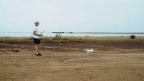 Jong geitje die een afstandsbediening houden en vliegende hommel controleren stock footage