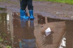 Jong geitje die een document boot zetten in water royalty-vrije stock afbeelding