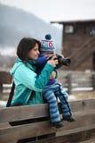 Jong geitje die een foto met moederholding hem nemen in wapens stock afbeelding