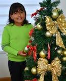 Jong geitje die een Kerstboom met snuisterijen verfraaien Stock Foto