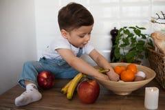 Jong geitje die een lijsthoogtepunt van natuurvoeding hebben Vrolijke peuter die gezonde salade en vruchten eten Baby die tussen  royalty-vrije stock foto