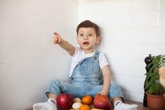 Jong geitje die een lijsthoogtepunt van natuurvoeding hebben Vrolijke peuter die gezonde salade en vruchten eten Baby die tussen  stock fotografie