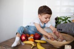 Jong geitje die een lijsthoogtepunt van natuurvoeding hebben Vrolijke peuter die gezonde salade en vruchten eten Baby die tussen  stock foto