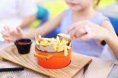 Jong geitje die gebraden aardappel, nadruk op Frieten eten royalty-vrije stock afbeeldingen