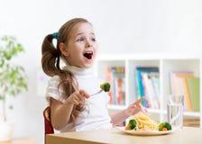 Jong geitje die gezond voedsel thuis of kleuterschool eten Stock Fotografie