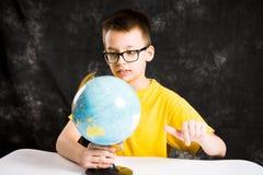Jong geitje die kleine bol op bureau bekijken Royalty-vrije Stock Foto