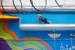 Jong geitje die op een buis met veiligheidsuitrusting beklimmen stock afbeeldingen