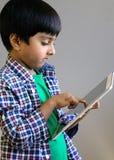 Jong geitje die op tabletcomputer onttrekken Kind dat tablet gebruikt Stock Foto