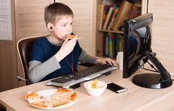 Jong geitje die pizza eten en op de videospelletjes van Internet surfen of het spelen stock afbeeldingen