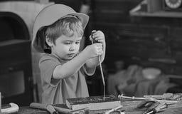 Jong geitje die schroevedraaier leren te gebruiken Geconcentreerd jong geitje in oranje helm die in workshop werken Toekomstig be royalty-vrije stock afbeeldingen