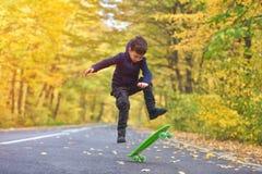 Jong geitje die skateboarder skateboardtrucs in de herfstmilieu doen royalty-vrije stock fotografie