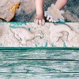Jong geitje die tot dierlijke vormen in sandpit leiden Stock Foto