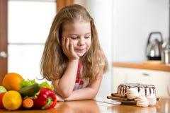Jong geitje die tussen gezonde groenten en smakelijke snoepjes kiezen Stock Fotografie