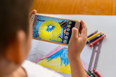 Jong geitje die Vergrote Werkelijkheids popup schilderijen van een gevulde berg via mobiel spelen Royalty-vrije Stock Afbeeldingen