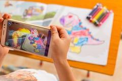 Jong geitje die Vergrote Werkelijkheids popup schilderijen van een gevulde dinosaurus via mobiel spelen royalty-vrije stock fotografie