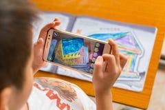 Jong geitje die Vergrote Werkelijkheids popup schilderijen van een gevulde tempel via mobiel spelen Stock Foto