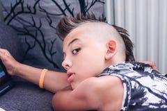 Jong geitje die youtube op zijn tablet letten op royalty-vrije stock afbeeldingen