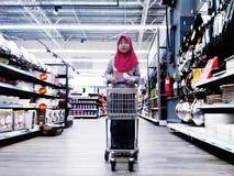 Jong geitje die zich met een karretje bij een supermarkt bevinden Stock Fotografie