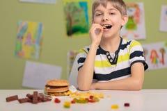 Jong geitje en ongezonde snacks stock afbeeldingen