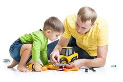 Jong geitje en zijn het stuk speelgoed van de papareparatie tractor Stock Fotografie