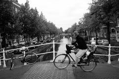 Jong geitje en zijn vader op fiets Stock Foto's