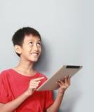 Jong geitje gebruikend tablet Stock Foto's