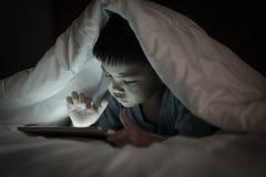 Jong geitje gebruikend tablet terwijl het liggen onder deken stock afbeelding