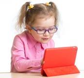 Jong geitje in glazen die het minischerm van tabletpc bij lijst bekijken royalty-vrije stock afbeeldingen