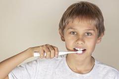 Jong geitje het borstelen tanden met witte elektrische tandenborstel stock afbeeldingen
