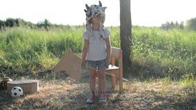 Jong geitje in het grappige dierlijke hoed spelen met houten stuk speelgoed paard stock video