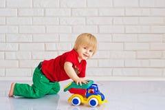 Jong geitje het spelen met een stuk speelgoed auto royalty-vrije stock foto