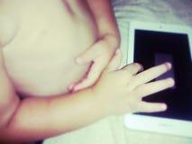 Jong geitje het spelen met een tablet Stock Fotografie