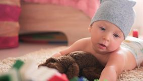 Jong geitje het spelen met gekleurde blokken van een aannemer op vloer in kinderenruimte stock video