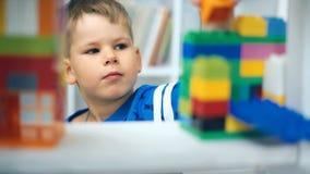 Jong geitje het spelen met logisch stuk speelgoed op vloer in kinderenruimte stock footage