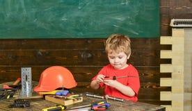 Jong geitje het spelen met rode schroevedraaier Kleine jongen in workshop Hulpmiddelen die op houten lijst liggen Stock Afbeeldingen